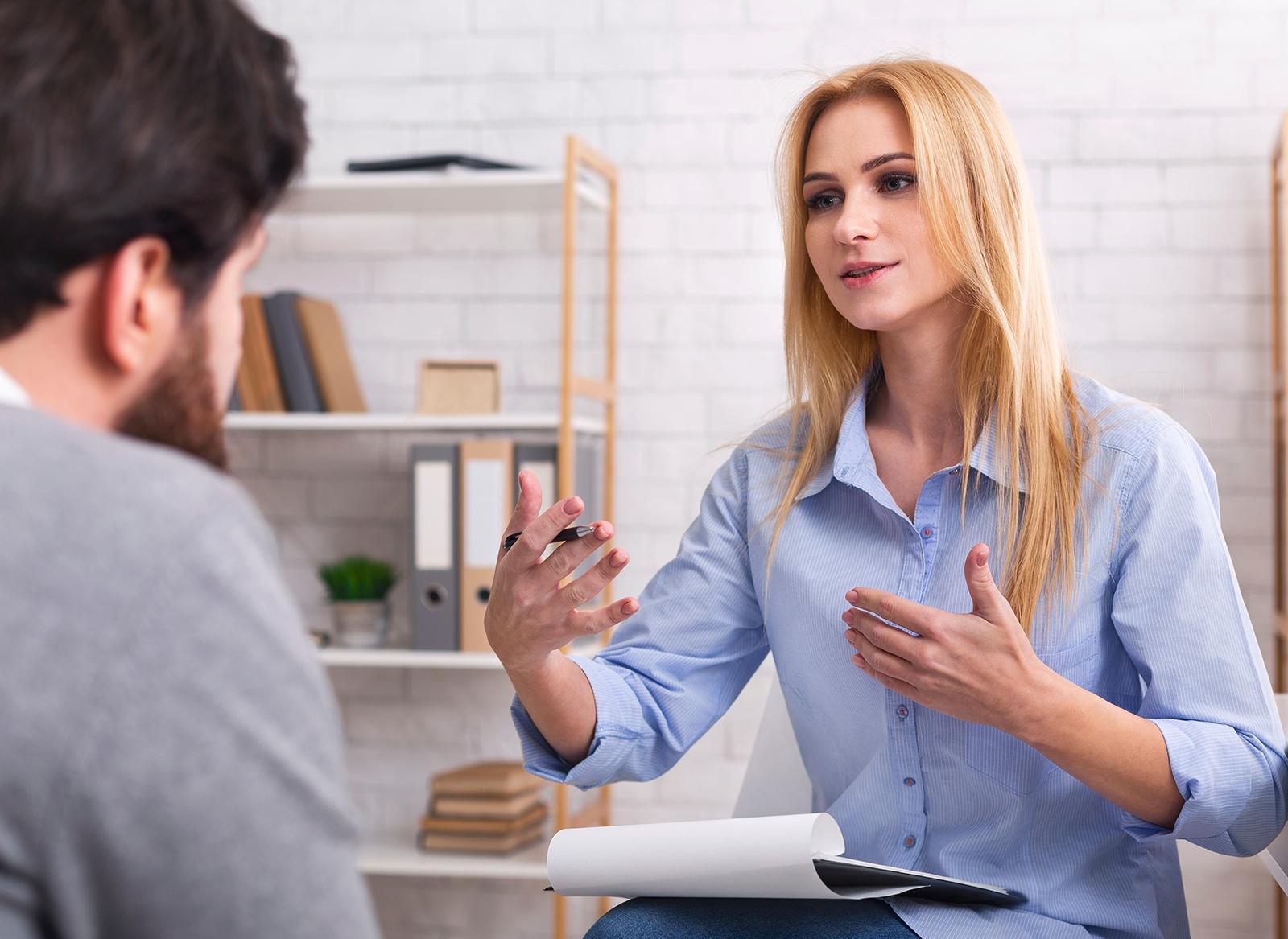 Frau als Sprachlehrerin sitzt ihrem Schüler gegenüber und erklärt ihm etwas, Szene aus einem der Sprachkurse Heilbronn